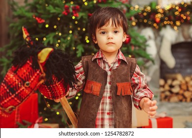 Close up warm portrait of small boy with dark messy hair, sweet beautiful face, dark big eyes, looking at camera, checked collar shirt, suede vest, holding hobbyhorse on stick, blurred background