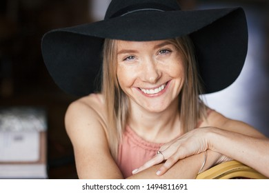 Close warm romantic portrait of a beautiful happy smiling young blonde woman with freckles in ash rose color dress and black felt hat. Girl sitting indoors