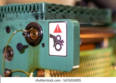 Up close of warning stickers stating to watch your hands and fingers for the moving part in this high speed industrial print machinery. Possible crushing and death due to injury from hazardous gears.