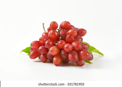 close up of washed red grapes on white background