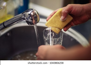close up washing dishes. male hands in foam washes the frying pan with a detergent and sponge in the kitchen of the house