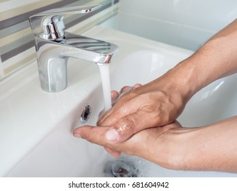 Close up of washing hands under running water at bathroom sink