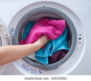 A close up of a washing machine loaded with clothes