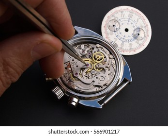close up of watchmaker adjusting watch