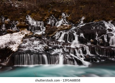 A close up of water cascading over lava rock formations into a turquoise blue river. Hraunfossar Waterfall, Iceland.