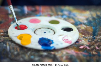 close up water color palette and brush on dirty table with color