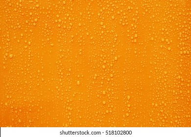 Close up water drop on orange background.