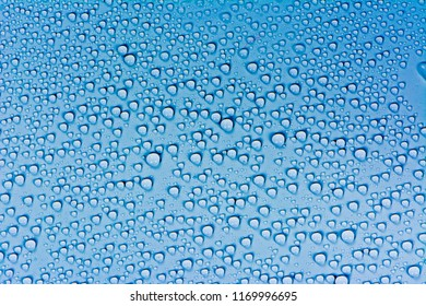 Close up water drops on dark blue tone background. Abstarct sky blue wet texture with bubbles on window glass surface. Raindrop, Realistic pure water droplets condensed for creative banner design