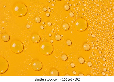 Close up of water drops on orange tone background. Abstarct yellow wet texture with bubbles on window glass surface. Raindrop, Realistic pure water droplets condensed for creative banner design. Brown
