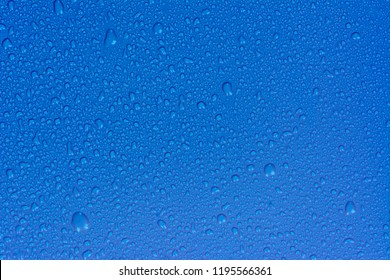 Close up water drops on sky blue tone background. Abstarct ultramarine wet texture with bubbles on window glass surface. Raindrop, Realistic pure water droplets condensed for creative banner design