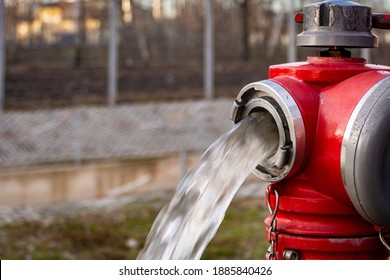 Close up of Water flowing from in open red fire hydrant