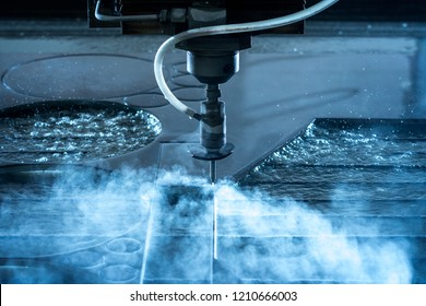 Close up of water jet cnc machine cutting steel with high water pressure for metalworking industry. Jet splash and drops flying.