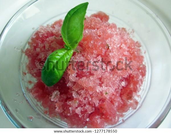 Close up of watermelon granita with basil leaf garnish