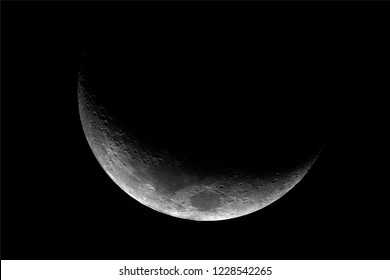 Close up of waxing crescent Moon with craters details, with dark background.
