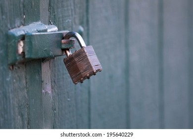 Close up of a weathered lock and bracket on a green barn door.