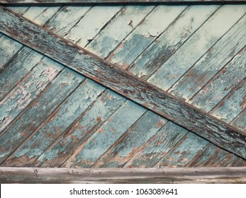 Close Up Of A Weathered Wooden Batten Door With A Z Brace And Peeling Paint