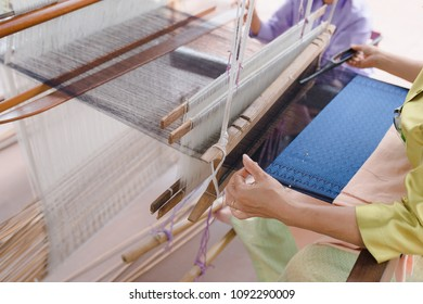 Close up of weaving  loom, cotton on the manual wood loom in Asian traditional culture and woman hand weave lifestyle