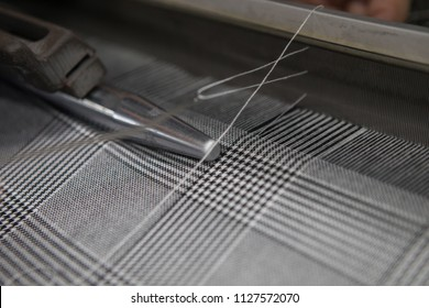 A close up of weaving machine. A loom machine for clothing or woven label. Weaving machine for garment industry. Weaving loom in textile factory. Industrial fabric production line in knitting machine.