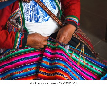Close up of weaving in Peru. Cusco, Peru   woman dressed in colorful traditional native Peruvian closing knitting a carpet with national pattern