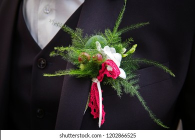 Close up of a wedding boutonniere on the bridegroom suit. The groom chest with green twigs and red berries in buttonhole. Beautiful buttonhole on a stylish lounge suit. Groom's suit accessories.