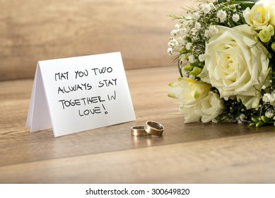 Close up Wedding Greeting Card with May You Two Always Stay Together In Love Message, Bouquet of Fresh White Flowers and a Pair of Rings on Top of a Wooden Table.