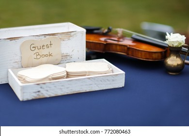 Close up of wedding guest book and violin on the table.