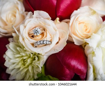 close up of wedding rings and flower bouquet