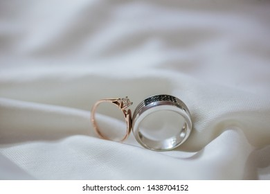 Close up of wedding rings on white silk with selective focus
