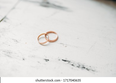 Close up of wedding rings on a white wooden old background