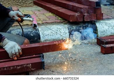 Close up welder hand welding steel at construction site.
