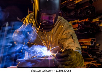 Close up welder is welding metal part in factory. Welder in protective uniform and mask welding metal pipe on the industrial