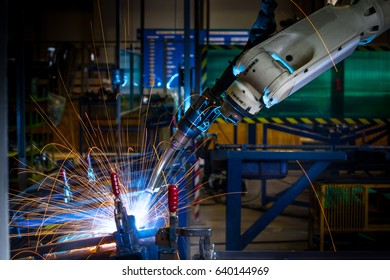 Close up welding robots working in a factory with spark represent the movement in the automotive parts industry.(manufacturing, industry, factory)