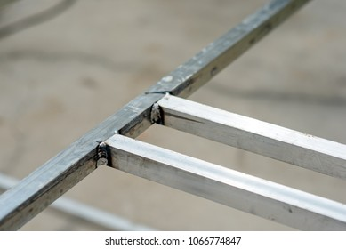 Close up of welds on square aluminum pipes