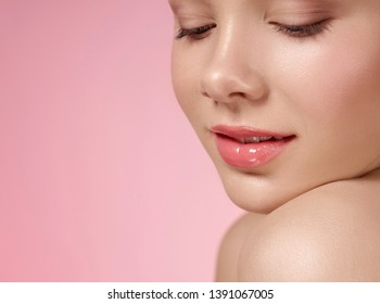 Close up of well groomed face of young, cute model with pink, wet lips, natural make up on pink background. Beautiful female head leaning on bare shoulder. Concept of skin care.