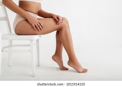 Close up of well groomed and graceful female feet posing on chair. Copy space in right side