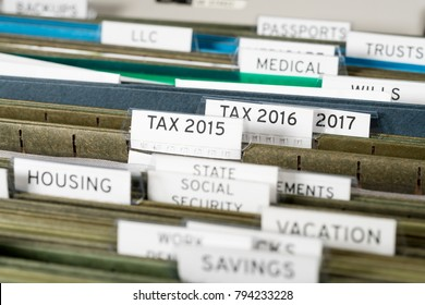 Close up of a well organized home filing system with tabs for each subject and focus on tax return papers