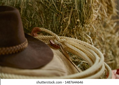 Close up of a western lasso with a cowboy hat and leather chaps on hay with shallow depth of field