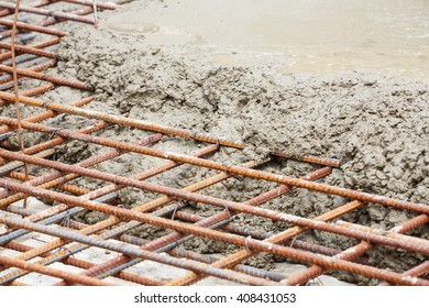 Close up wet cement pour on deformed steel bars with tie wires in construction site, floor pouring
