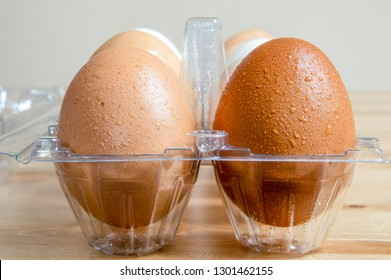 Close up of wet clean chicken eggs in a plastic box on a table.