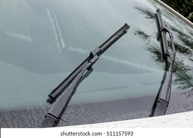 Close up of wet windshield reflections patterns textures and wiper blades and arms