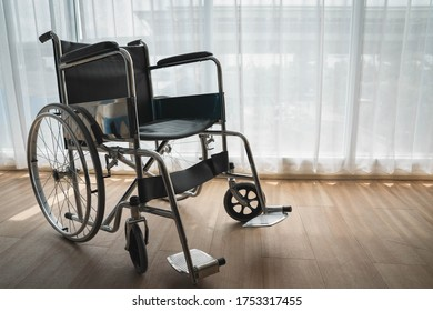 Close up wheel chair in front of the window with light and shadow.