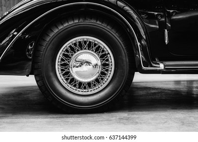 A close up of wheel disk and the side of a vintage automobile.