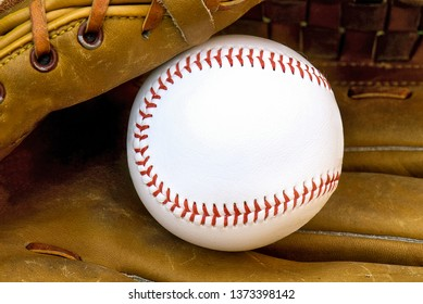 close up of white baseball in brown leather glove with copy space