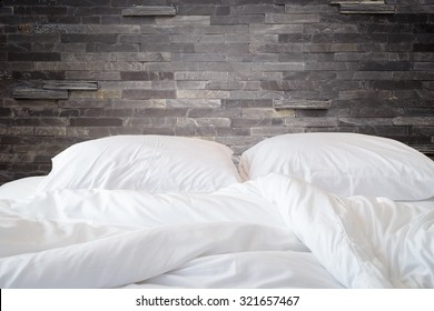 eb1327400c Close up white bedding sheets and pillow on natural stone wall room  background