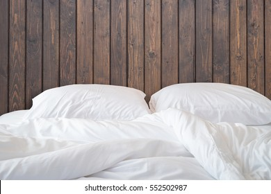 Close up white bedding sheets and pillow on wooden wall room background, Messy bed concept .