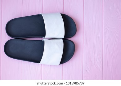 Close up of white and black rubber slippers on an pink background. Slippers for the sea.