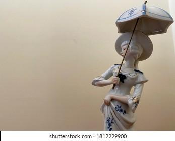 Close up to a white and blue porcelain woman shape trinket