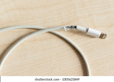 Close up the white broken smartphone usb cable on white wooden background.