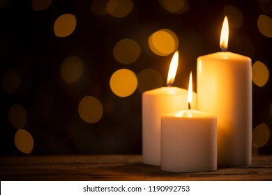 Close up of white burning candles on the table with golden light background blur
