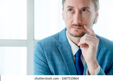 close up white caucasian senior businessman with beard in blue suit with tie wait and thinking hand gesture white frame window background